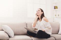 Mujer de risa joven en casa con el ordenador portátil y el móvil Imagen de archivo libre de regalías
