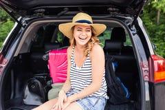 Mujer de risa joven que se sienta en el tronco abierto de un coche Viaje por carretera del verano Fotografía de archivo