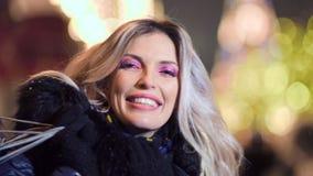 Mujer de risa de la cara del primer con los bolsos de compras en el fondo colorido de la Navidad del bokeh de las luces almacen de video