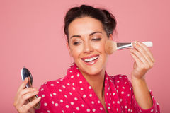 Mujer de risa que aplica blusher Fotografía de archivo