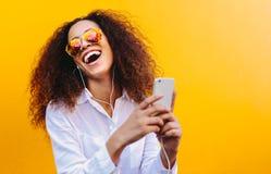 Mujer de risa que disfruta de música que escucha imagenes de archivo