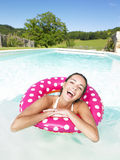 Mujer de risa que flota en piscina Foto de archivo libre de regalías