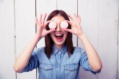 Mujer de risa que la cierra ojos con las galletas redondas Imagenes de archivo