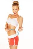 Mujer de risa que mide su cintura Imagen de archivo