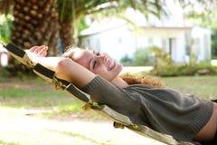 Mujer de risa que miente en hamaca fuera de la casa Imagenes de archivo