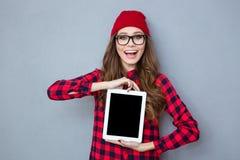 Mujer de risa que muestra la pantalla de tableta en blanco Fotografía de archivo