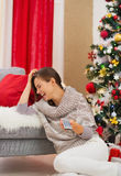 Mujer de risa que ve la TV cerca del árbol de navidad Imagen de archivo libre de regalías