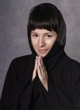 Mujer de rogación en vestido negro con la capilla en un fondo gris Foto de archivo libre de regalías