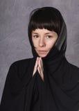 Mujer de rogación en vestido negro con la capilla en un fondo gris Imagen de archivo