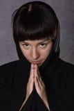 Mujer de rogación en vestido negro con la capilla en un fondo gris Foto de archivo