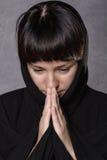 Mujer de rogación en vestido negro con la capilla en un fondo gris Fotos de archivo libres de regalías
