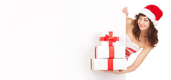 Mujer de Santa con los rectángulos de regalo que miran a la tarjeta en blanco Foto de archivo libre de regalías