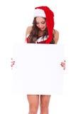 Mujer de Santa que mira a una tarjeta en blanco Imagen de archivo libre de regalías