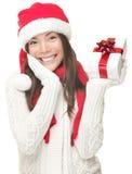 Mujer de Santa que muestra el regalo que sonríe - la Navidad Fotografía de archivo libre de regalías