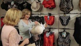Mujer de Shopaholic que intenta el sombrero elegante encendido en tienda almacen de metraje de vídeo