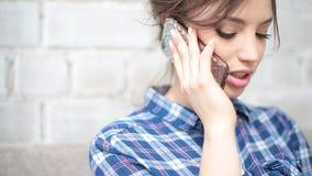 Mujer de Smartphone que habla en el café de consumición del teléfono que ríe en café Profesional femenino joven multicultural her almacen de video