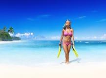 Mujer de Smilig con el engranaje de equipo de submarinismo en una playa tropical Foto de archivo