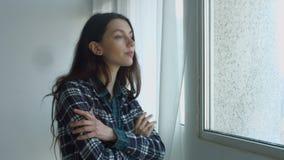 Mujer de sueño sensual que mira hacia fuera la ventana almacen de metraje de vídeo