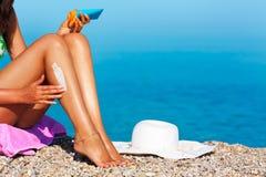 Mujer de Tan que aplica la protección solar en sus piernas Imágenes de archivo libres de regalías