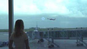 Mujer de Travling que mira al aeroplano de la ventana del aeropuerto mientras que espera en salón de la salida Turista de la muje almacen de metraje de vídeo
