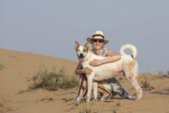 Mujer de Yong con un perro en un desierto Fotografía de archivo