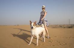 Mujer de Yong con un perro en un desierto Fotos de archivo