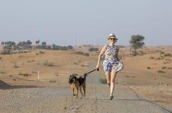 Mujer de Yong con un perro en un desierto Fotos de archivo libres de regalías
