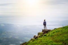 Mujer de Yong que se coloca en el top de la montaña observando Fotografía de archivo libre de regalías