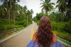 Mujer de Youg que camina en el camino entre las palmeras tropicales en Tailandia fotos de archivo libres de regalías