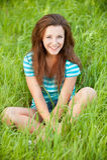 Mujer de Youngl que se sienta en hierba verde Foto de archivo libre de regalías
