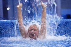 Mujer debajo de la corriente del agua en la piscina fotos de archivo