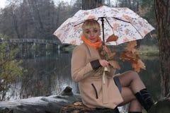 Mujer debajo de un paraguas, última caída, lago del bosque imagen de archivo