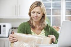 Mujer decepcionada que desempaqueta la compra en línea en casa Foto de archivo