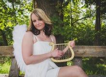 Mujer del ángel con la arpa Fotografía de archivo libre de regalías