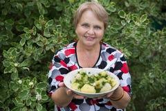 Mujer del abuelo con las patatas hervidas en la placa Foto de archivo libre de regalías