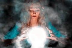 Mujer del adivino con la esfera ligera en sus manos fotografía de archivo libre de regalías
