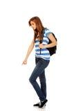 Mujer del adolescente con la mochila que señala para soomething Fotos de archivo libres de regalías