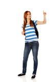 Mujer del adolescente con la mochila que señala para soomething Foto de archivo libre de regalías