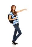 Mujer del adolescente con la mochila que señala para soomething Imágenes de archivo libres de regalías
