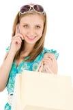 Mujer del adolescente de las compras con el teléfono móvil Foto de archivo libre de regalías