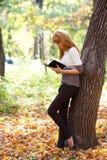 Mujer del adolescente del Redhead que lee un libro Foto de archivo libre de regalías