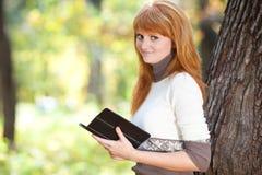 Mujer del adolescente del Redhead que lee un libro Fotos de archivo