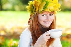 Mujer del adolescente en una guirnalda de hojas de arce con Cu Fotos de archivo