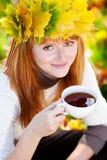 Mujer del adolescente en una guirnalda de hojas de arce con Cu Fotos de archivo libres de regalías