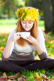 Mujer del adolescente en una guirnalda de hojas de arce con Cu Imagenes de archivo