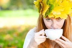 Mujer del adolescente en una guirnalda de hojas de arce con Cu Foto de archivo