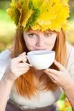 Mujer del adolescente en una guirnalda de hojas de arce con Cu Foto de archivo libre de regalías