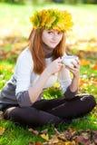 Mujer del adolescente en una guirnalda de hojas de arce con Cu Fotografía de archivo libre de regalías