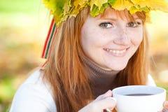 Mujer del adolescente en una guirnalda de hojas de arce con Cu Imagen de archivo