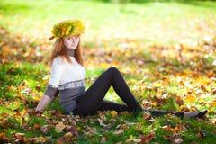 Mujer del adolescente en una guirnalda de las hojas de arce o de mentira Imagen de archivo libre de regalías